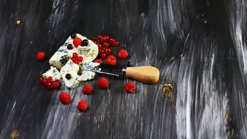 Roquefort do queijo azul com bagas e a faca frescas do queijo no fundo de pedra do preto escuro Copie o texto fotos de stock royalty free