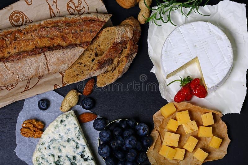 Roquefort, DorBlu, camembert och andra ostar med bröd som smakar med bär, muttrar, mellanmål, stor formatupplösning Matbaner för fotografering för bildbyråer