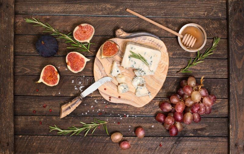 Roquefort eller ädelost som tjänar som med druvor, honung och fikonträd Olika typer av ost p? en tr?bakgrund royaltyfria bilder