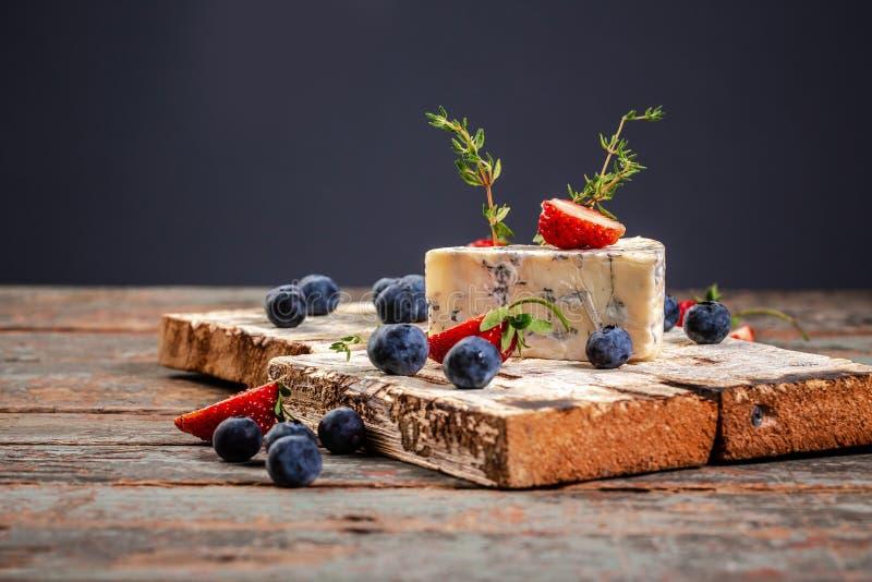 Roquefort fransk ädelost med formen på en träyttersida som tjänas som med blåbäret och jordgubben arkivfoton