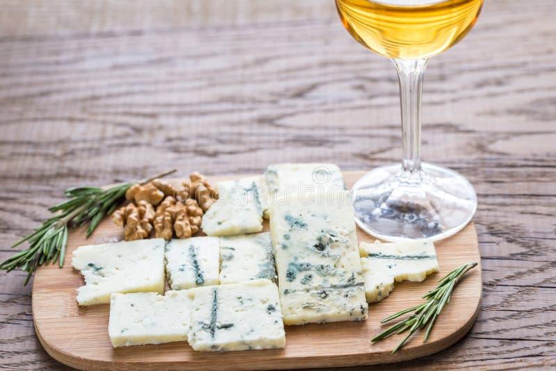Roquefort med exponeringsglas av vitt vin på träbrädet royaltyfria foton