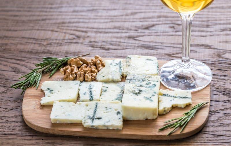 Roquefort med exponeringsglas av vitt vin på träbrädet arkivfoton