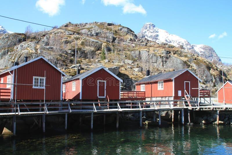 Rorbuer três velho que espelha em Nusfjord foto de stock