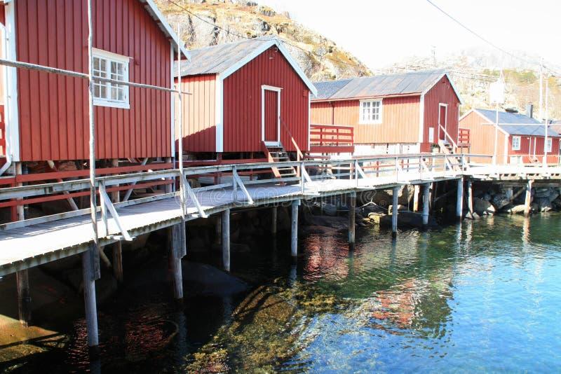 Rorbuer trois reflétant dans Nusfjord photographie stock