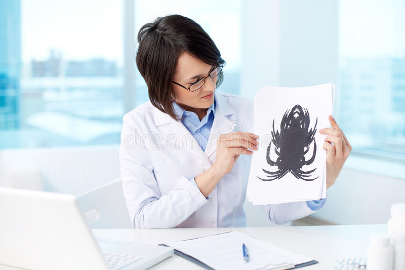 Rorschach test. Young psychologist looking at paper with Rorschach inkblot royalty free stock images