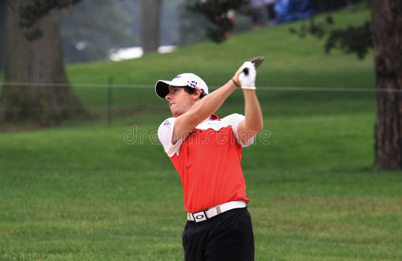 Rory McIlroy PGA pro. Rory McIlroy of Ireland swings his driver club as the crowd watches royalty free stock image