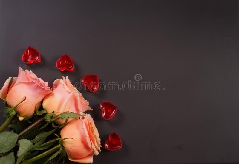 Ros för tre beiga med stearinljus i formen av hjärta på en mörk träbakgrund med kopieringsutrymme för din text royaltyfri foto
