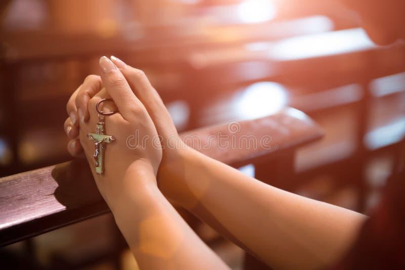 Ros?rio da terra arrendada da m?o da mulher contra a cruz e rezar ao deus na igreja fotos de stock