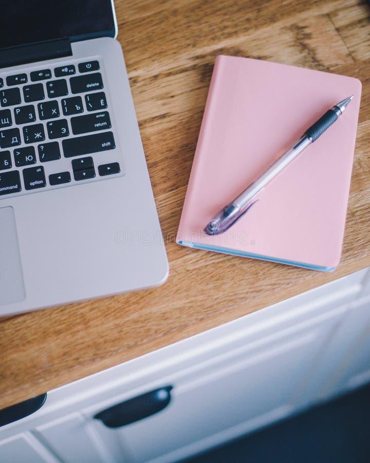 Rosa anteckningsbok f?r n?rbild med penn- och b?rbar datorl?gn p? en tr?tabell fotografering för bildbyråer