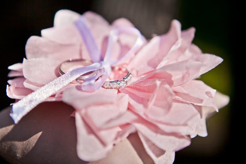 Rosa artificial con los anillos de bodas, foco selectivo del rosa del primer foto de archivo libre de regalías