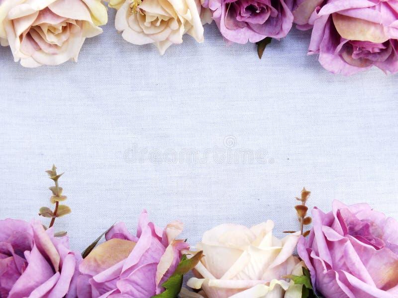A rosa artificial do roxo floresce no fundo de linho da beira do espaço da cópia imagens de stock royalty free