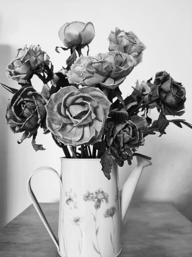 rosa artificial en un jarrón de zinc colocado en una mesa decorativa de salón imagen de archivo libre de regalías