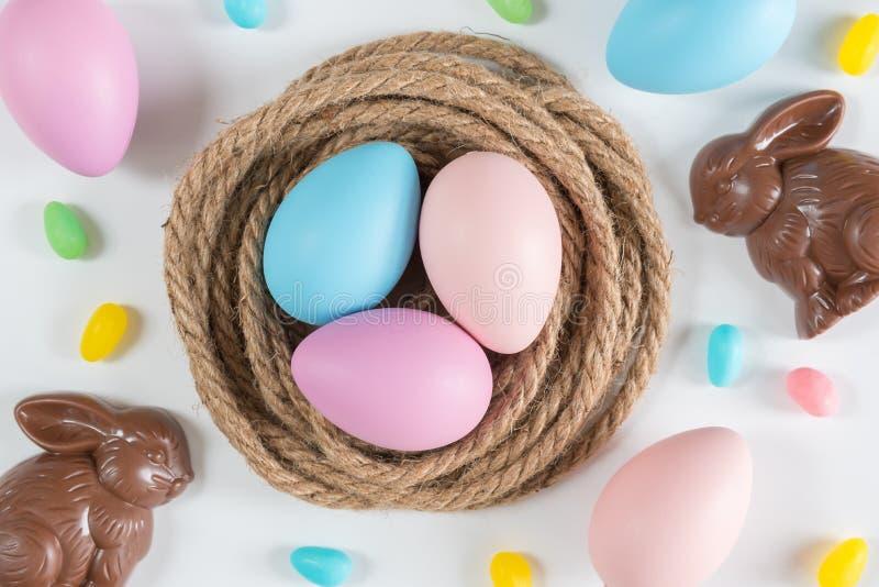 Rosa, azul, y huevos de Pascua púrpuras en jerarquía con los conejos y los jellybeans del chocolate fotos de archivo libres de regalías