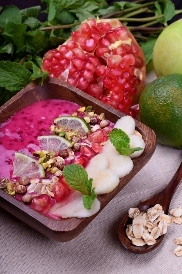 Rosa bärsmoothie som garneras med äpplet, limefrukt, granatäpplet, pistaschmuttrar och havremjölflingor fotografering för bildbyråer