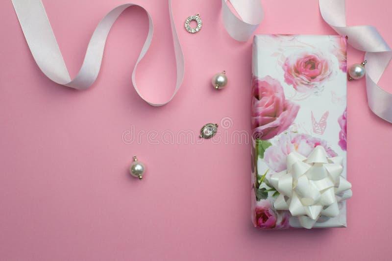 Rosa bakgrund för moderdag med den slågna in gåvan, vit satängribbo arkivbilder