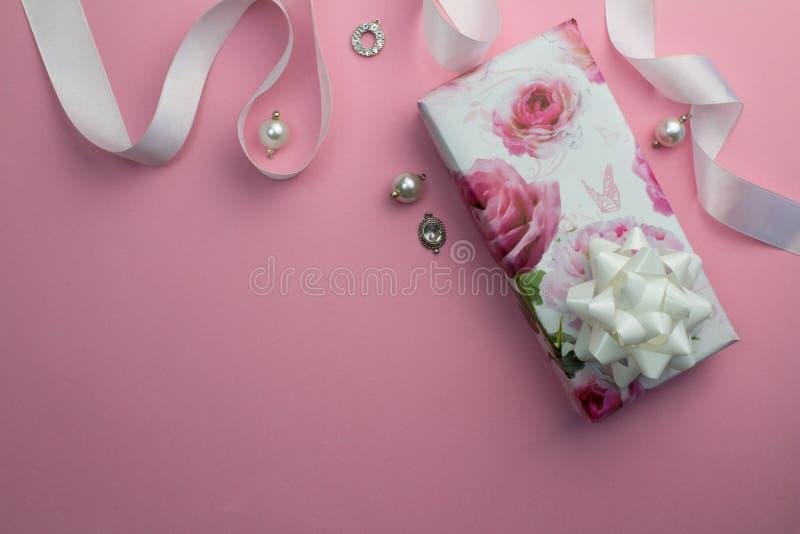 Rosa bakgrund med den slågna in gåvan, det vita satängbandet och pärlan royaltyfri foto