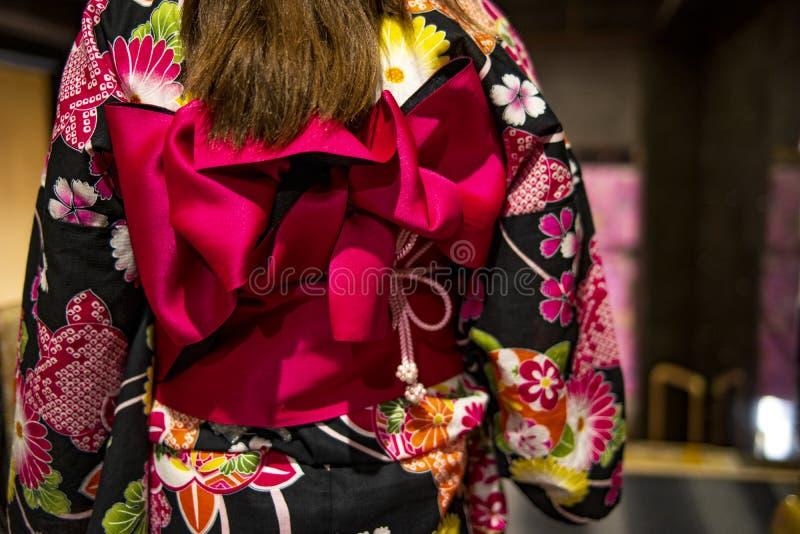 Rosa Band auf japanischer traditioneller Kleidung des Kimonos Junges Mädchen, das japanischen Kimono trägt Kleiden des Kimonos lizenzfreies stockfoto