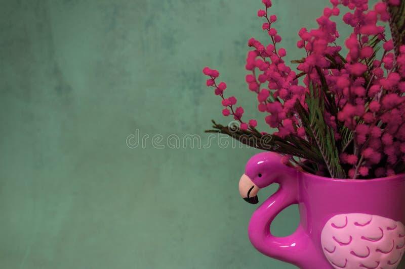 Rosa Becher- oder Blumentopf Flamingoform mit rosa Mimose auf einem dunklen grünen Smaragdhintergrund stockfoto