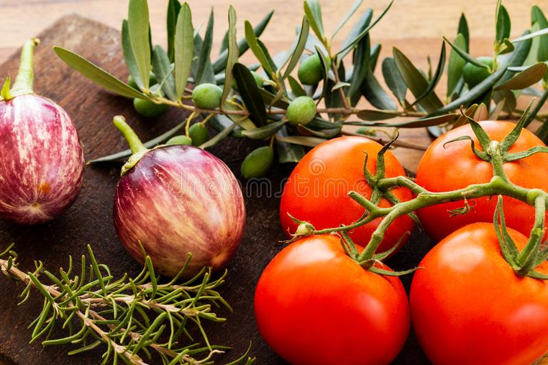Rosa Bianca eggplants with tomatoes on branch over a wooden board with green olives on branch with leaves and rosemary twig. stock image