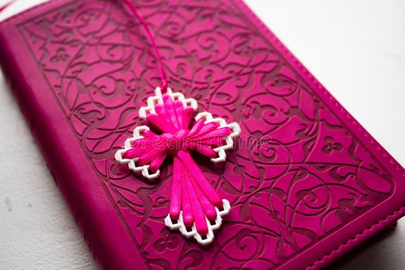 Rosa Bibel mit handgemachtem rosa Kreuz auf ihm lizenzfreie stockbilder