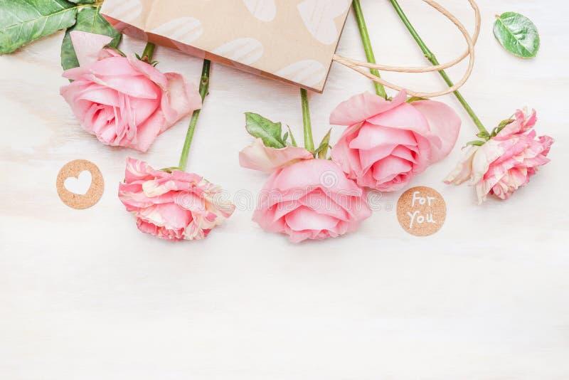 Rosa bleka rosor skyler över brister shoppingpåsen och rundatecknet med meddelandet för dig och hjärta på vit träbakgrund, bästa  royaltyfri foto