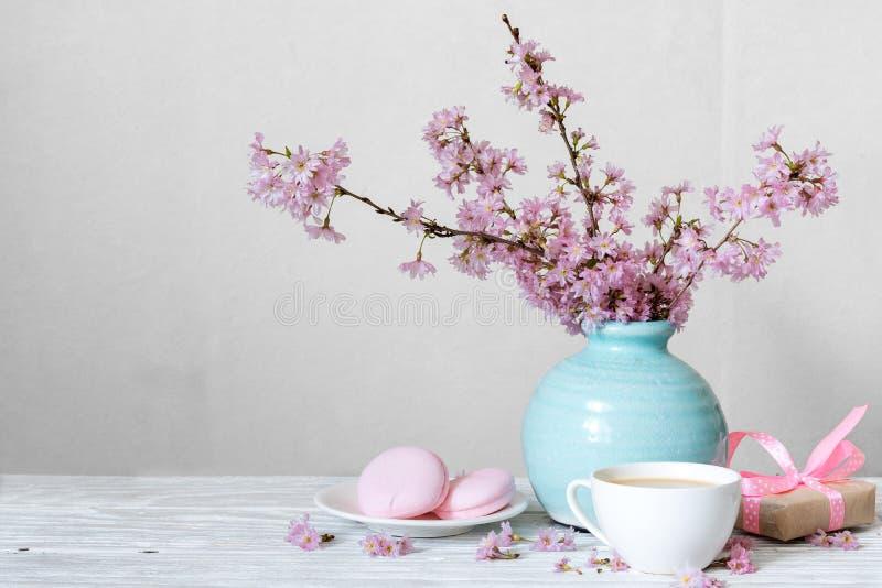 Rosa blommabukett för körsbärsröd blomning med kaffekoppen, makron och gåvaasken i blå tappningvas fotografering för bildbyråer