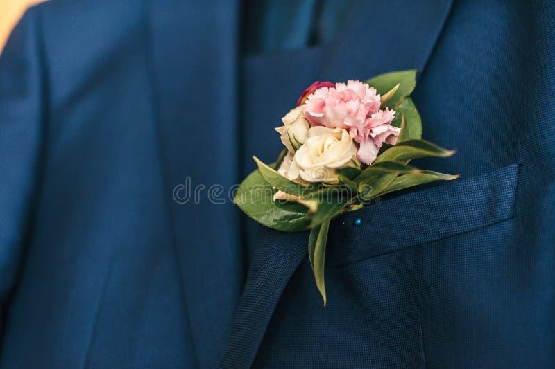 Rosa blommor i knapphålet av brudgummen arkivbild