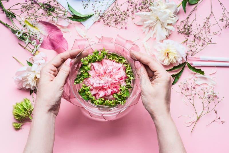 Rosa blomsterhandlareworkspace med liljor och annan blommar, den glass vasen med vatten Kvinnlign räcker framställning av festlig royaltyfri foto