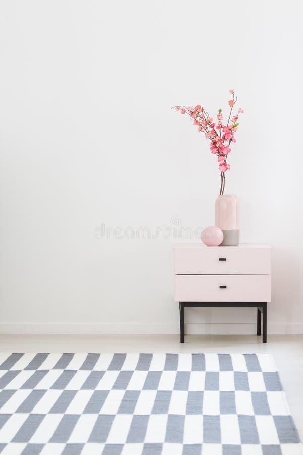 Rosa Blumen auf Kabinett im weißen Wohnzimmerinnenraum mit patte stockfoto