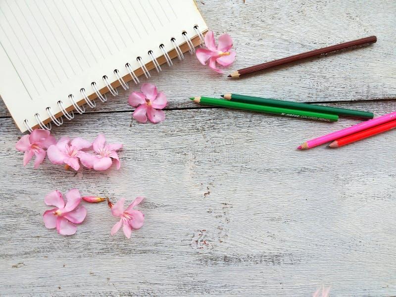 rosa Blumen und Bleistift des Notizbuches auf hölzernem Hintergrund stockbild