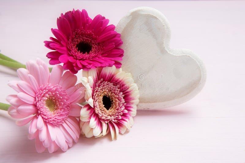 Rosa Blumen und ein Weiß malten hölzernes Herz auf einem Pastell-colore lizenzfreie stockfotografie