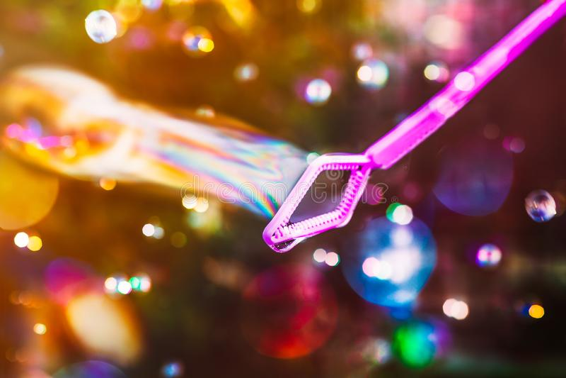 Rosa bubblatrollstav som dras till och med luften som skapar en ström av tvåliga färgglade bubblor som fångar det ljuset och skap arkivfoto