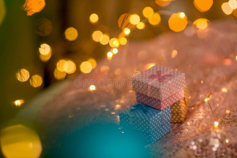 Rosa, café e presentes azuis em um fundo brilhante coral com luzes douradas borradas imagem de stock