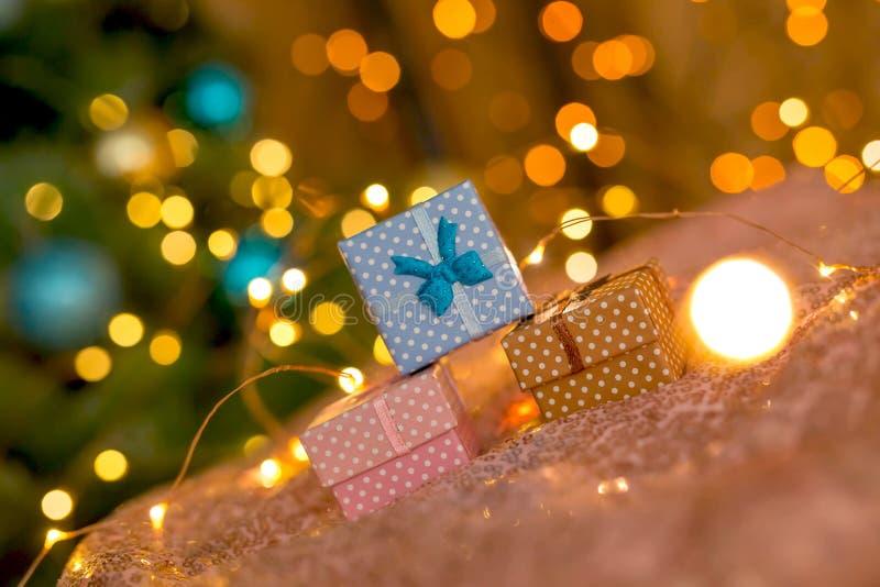 Rosa, café e presentes azuis em um fundo brilhante coral com luzes douradas borradas imagens de stock royalty free