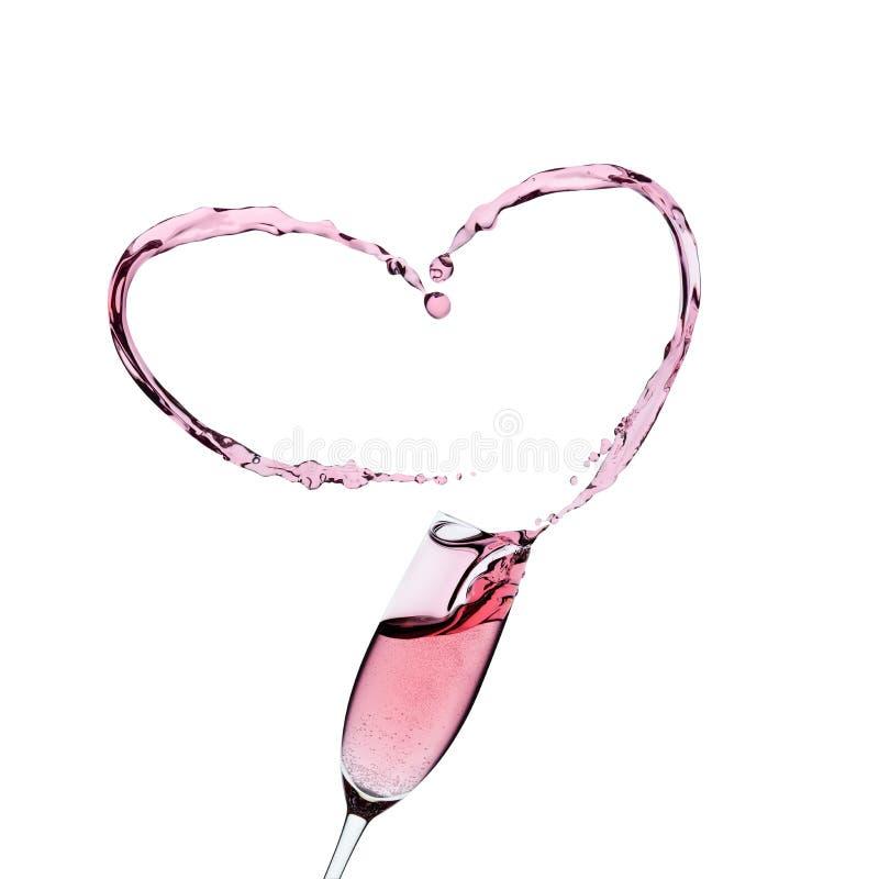 Rosa champagneexponeringsglas med en färgstänk arkivfoto