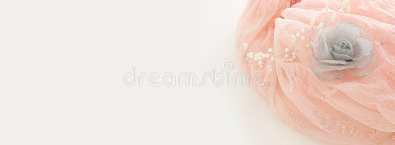 Rosa Chiffon- Kleid Weinlesetulles auf hölzerner weißer Tabelle Hochzeit und girl& x27; s-Parteikonzept stockfotos