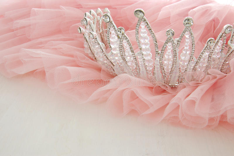 Rosa Chiffon- Kleid Weinlesetulles und Diamanttiara auf hölzerner weißer Tabelle Hochzeit und girl& x27; s-Parteikonzept lizenzfreie stockfotos