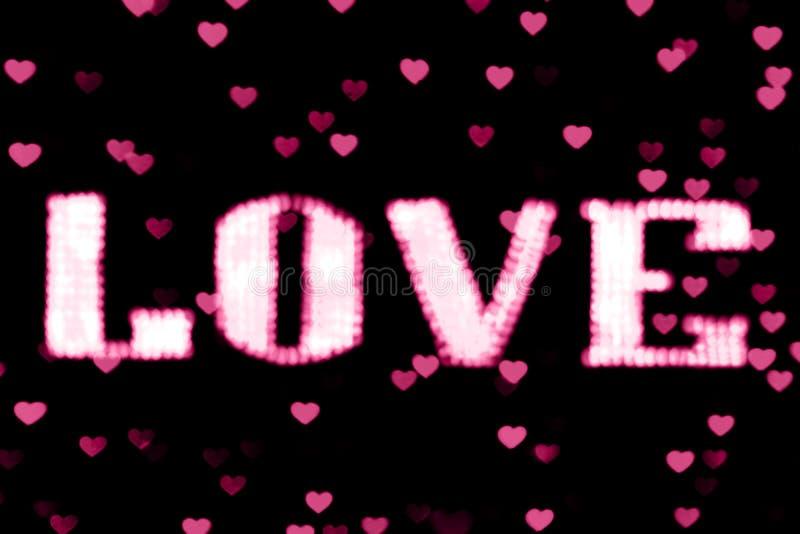 Rosa claro de neón borroso de la muestra LED de Bokeh del AMOR del rosa del texto en bokeh del fondo enciende el corazón suavemen imagenes de archivo