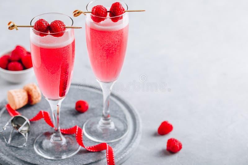Rosa Cocktail mit Champagner oder Prosecco und frische Himbeeren für den Valentinstag stockfoto