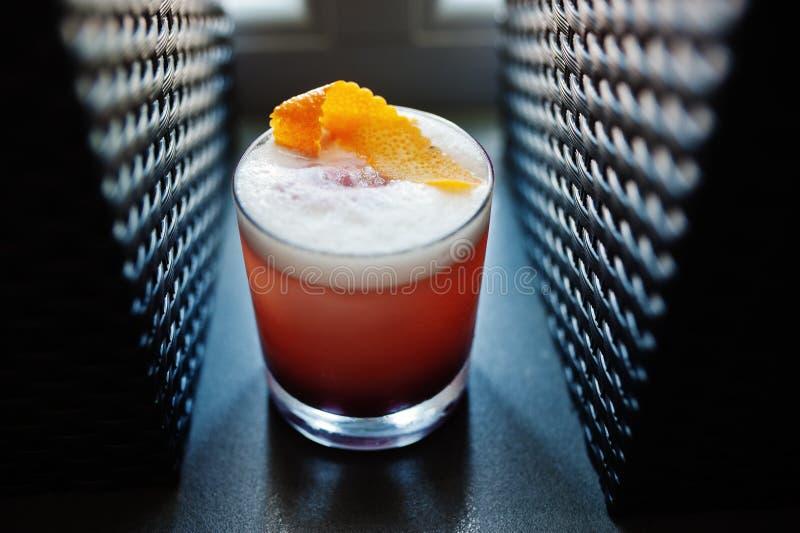 Rosa coctail för alkoholist i exponeringsglas på stångtabellen arkivfoton