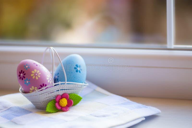 Rosa colorido e ovos da páscoa azuis na cesta com a flor decorativa perto da janela na luz do dia imagens de stock royalty free