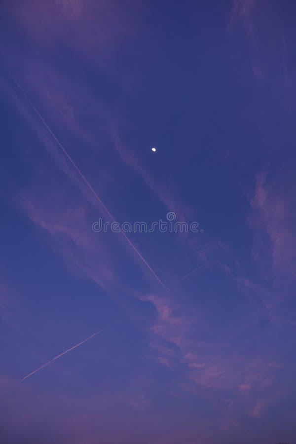 Rosa Contrailkondensstreifen und -wolken auf einem Sonnenunterganghimmel mit Mond im Hintergrund stockfotografie