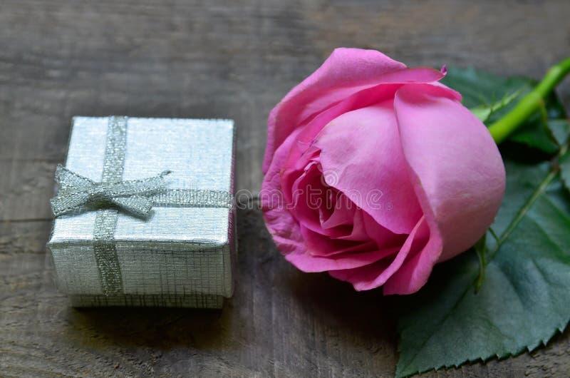 Rosa cor-de-rosa e caixa de presente de prata no fundo de madeira velho O dia de MotherÂ, o dia das mulheres, conceito do cartão  foto de stock