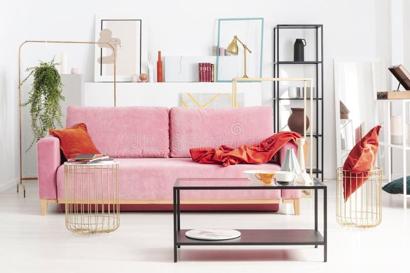 Rosa Couch des Pulvers mit rotem Kissen und Decke in der Wohnung voll der Kunst und der Regale stockbilder