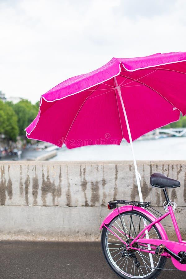 Rosa cykel med paraplyet Cykel under ett rosa paraply på bakgrunden av ett konkret staket arkivfoto