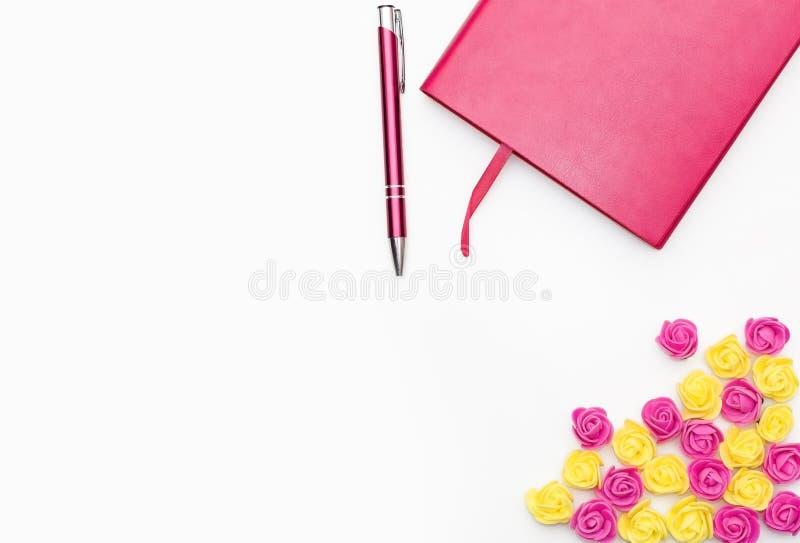 Rosa dagbok med en penna och små gula rosa rosor på en vit bakgrund arkivbilder