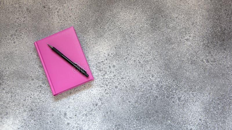 Rosa dagbok och blyertspenna på en grå konkret bakgrund fotografering för bildbyråer