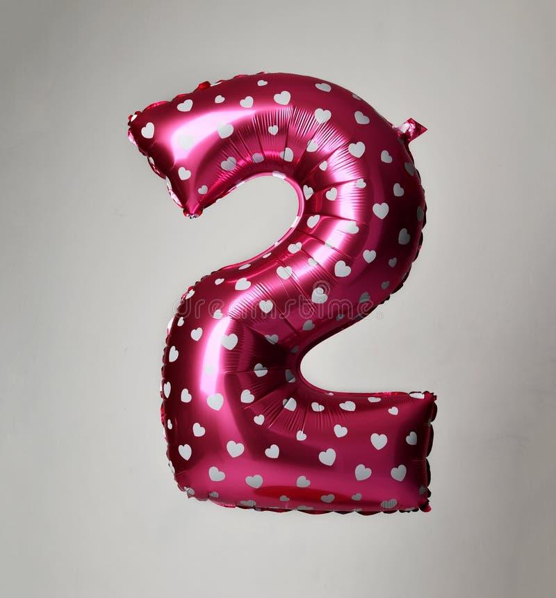 Rosa de dos dígitos rosado enorme del globo con los corazones como presente para la fiesta de cumpleaños imagen de archivo libre de regalías