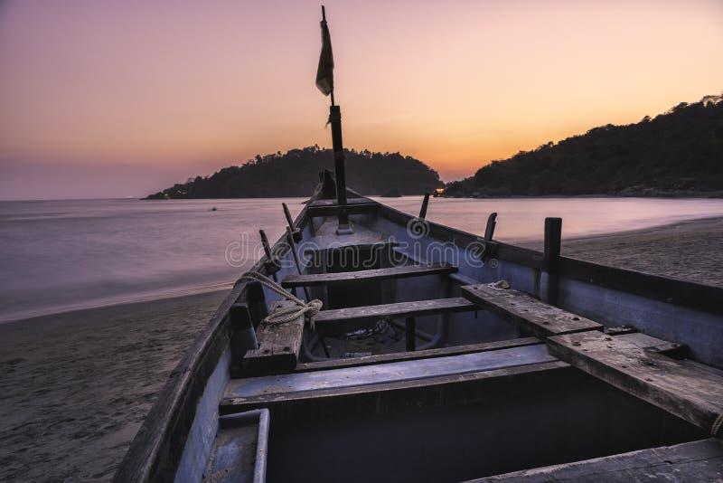 Rosa del colorfull de la puesta del sol y violeta en un goa tropical la India de la playa con el barco y la isla azules imágenes de archivo libres de regalías