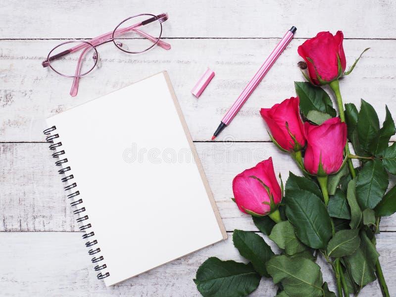 Rosa del cuaderno de notas con eyeglases y rosas foto de archivo